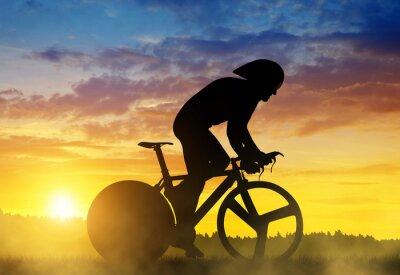 Canvastavlor Silhuett av en cyklist på en racercykel vid solnedgången.
