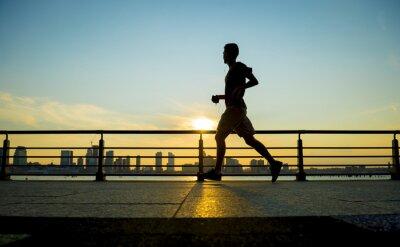 Canvastavlor Silhuett av joggare kör på solnedgången framför stadens silhuett