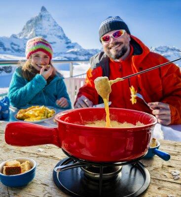 Canvastavlor Skidåkare i en restaurang, Fondue, traditionella schweiziska skålen - Matter i schweiziska Alperna i bakgrunden
