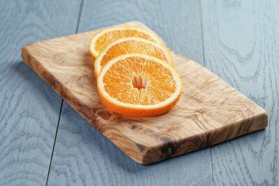 Canvastavlor skivor mogen orange på oliv skärbräda, ytlig fokus