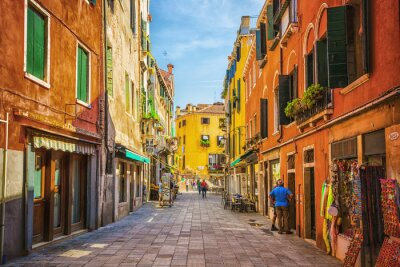 Canvastavlor Smal kanal bland gamla färgrika tegelhusen i Venedig