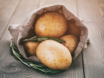 Canvastavlor småpotatis i säck väska med rosmarin på trä bord, vintage tonade