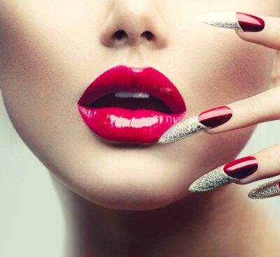 Canvastavlor Smink och manikyr. Röda långa naglar och röda glansiga läppar