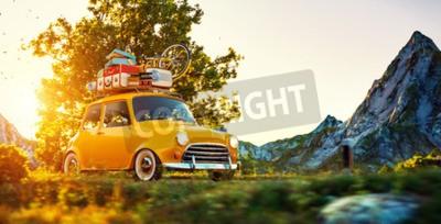 Canvastavlor Söt liten retro bil med resväskor och cykel på toppen går genom underbar landsbygdsväg vid solnedgången