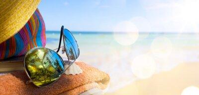 Canvastavlor Stråhatt, väska och solglasögon på en tropisk strand