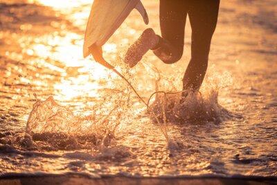 Canvastavlor Surfare som körs i vattnet med sin styrelse