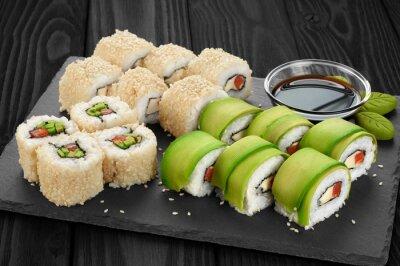 Canvastavlor Sushi rullar med avokado, lax och sesamfrön på skiffer facket.
