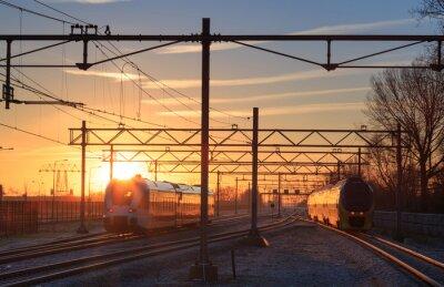 Canvastavlor Tåg som lämnar en station under en vinter soluppgång.