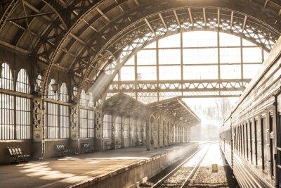 Canvastavlor Tågstation inomhus solnedgång soluppgång i sepia. Vagn och plattform med byggnadstak. Resa på tåg på järnväg