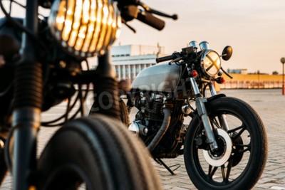 Canvastavlor Tappning anpassade motorcykel café racer motorcykel med lampan lyser påslagen. En med grill strålkastare varandra med tejp cross over optik på tom taket parkeringsplats under solnedgång. Hipster livss