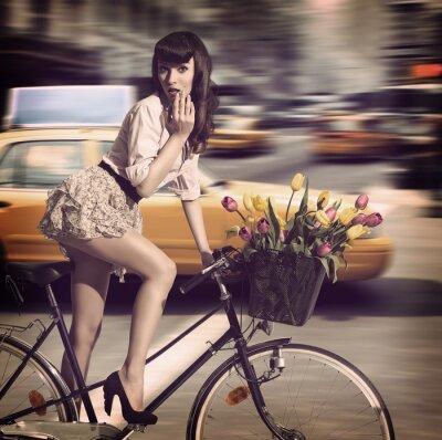 Canvastavlor tappning kvinna på cykel i en stadsgata med taxi