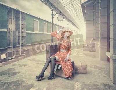 Canvastavlor Tjejen sitter på resväskan och väntar på retro järnvägsstationen. Vintage färg kort stil