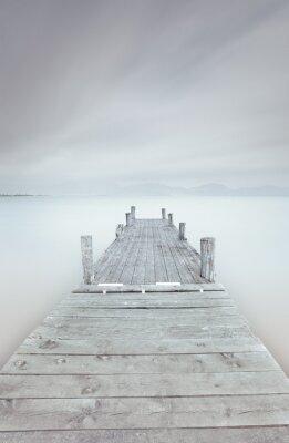 Canvastavlor Träbrygga på sjön i en molnig och dimmig humör.