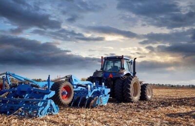 Canvastavlor Traktor som arbetar i fältet vid solnedgången