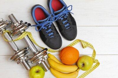 Canvastavlor träningsredskap och hälsosam kost på vit planka fl