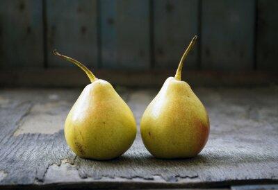 Canvastavlor Två gula päron tvillingar på trägolv, stilleben