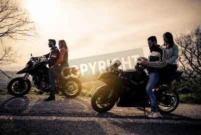 Canvastavlor Två motorcyklar kör i naturen - vänner kör racing motorcyklar med sina flickvänner - gruppen cyklister stannar i en panoramavy punkt och titta på suggestiva solnedgången