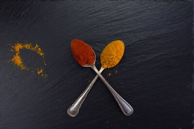 Canvastavlor Två vintage skedar med kryddor curry och paprika på svart bakgrund.
