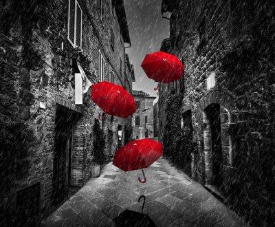 Canvastavlor Umrbellas flyger med vind och regn på mörk gata i en gammal italiensk stad i Toscana, Italien