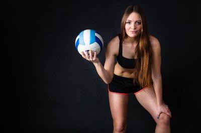 Canvastavlor Ung flicka som innehar volleyboll på svart bakgrund