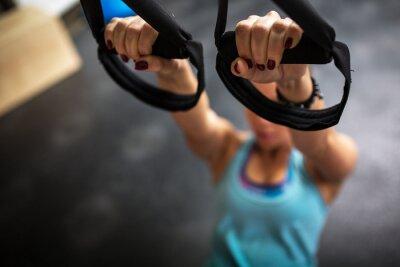 Canvastavlor Ung kvinna vid gym arbetar på hennes magmuskler på TRX