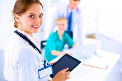 Canvastavlor Ung kvinnlig läkare som innehar en tablet pc
