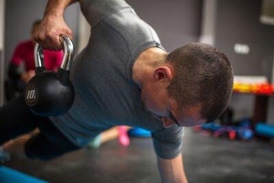 Canvastavlor Ung man lyft hantel och kettlebell på gymmet