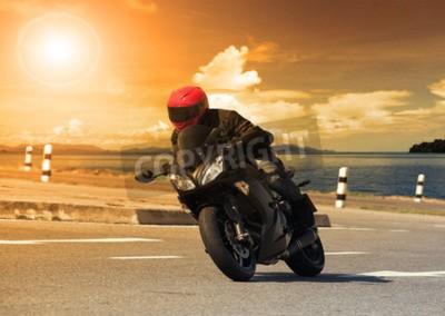 Canvastavlor ung man rider stor cykel motorcykel mot skarp kurva av asfalt hög sätt vägen med landsbygd sjö scen användning för manliga äventyrsaktiviteter och motorsport hobby på semester semester