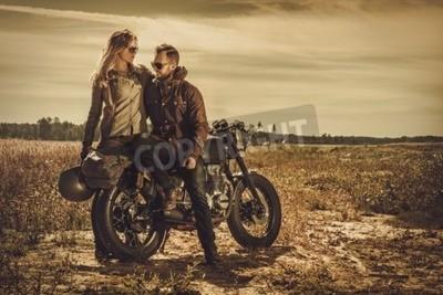 Canvastavlor Unga, snygga cafe racer par på vintage anpassade motorcyklar i ett fält.