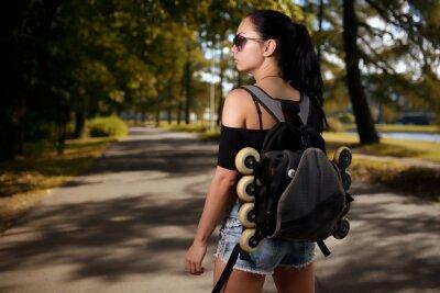 Canvastavlor Vacker flicka brunett med ryggsäck bakom ryggen på vilka rullskridskor