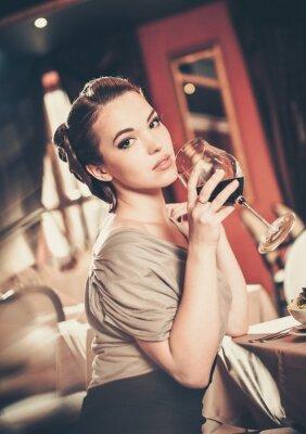 Canvastavlor Vacker ung flicka med glas rött winein en restaurang