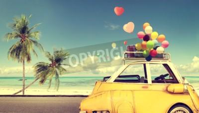 Canvastavlor Vintage gul bil med hjärtans färgstarka ballong på stranden blå himmel - begrepp kärlek på sommaren och bröllop. Smekmånad resa