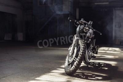 Canvastavlor Vintage motorcykel står i en mörk byggnad i solstrålarna. Tonade färger. Frontvy