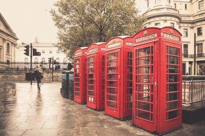 Canvastavlor Vintage stil röda telefonkiosker på regnig gata i London