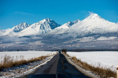 Canvastavlor Vinterkörning - vinterväg Landsväg leder genom en vinter bergslandskap.