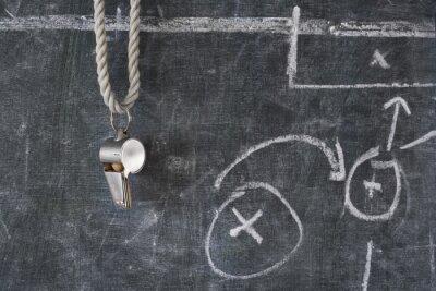 Canvastavlor vissling fotboll eller fotbollsdomare på en svarta tavlan med taktiska diagram