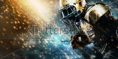 Fototapet American football sportsman player on stadium running in action. Sport wallpaper with copyspace.