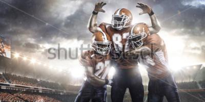 Fototapet Amerikanska fotbollsspelare i action på stadionens panoramautsikt
