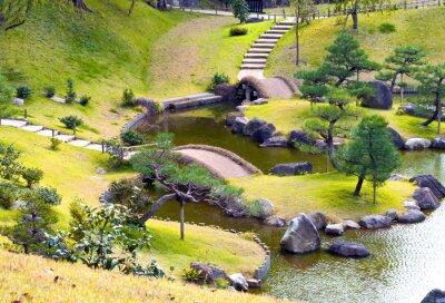 Fototapet Anlagd kuperad sten med små broar över slingrande ström, uppförsbacke steg, tallar