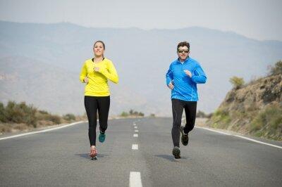 Fototapet attraktiv sport par man och kvinna som kör tillsammans på asfaltväg fjällandskap