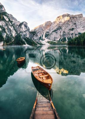 Fototapet Båtar och glidkonstruktion i Braies sjö med kristallvatten i bakgrunden av Seekofelbergen i Dolomiterna på morgonen, Italien Pragser Wildsee