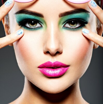 Fototapet Beautiful Face of a woman with green vivid make-up of eyes