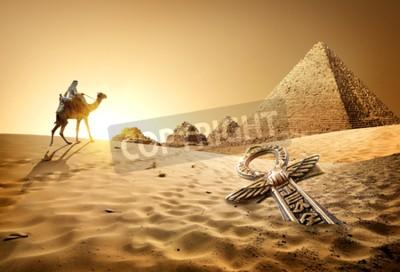 Fototapet Beduin på kamel nära pyramiderna och ankh i öknen
