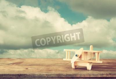 Fototapet Bild av träleksak flygplan över träbord mot molnig himmel. Retro stil bild