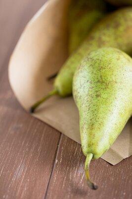 Fototapet Birnen fallit aus einer Obsttüte auf ein Holzbrett
