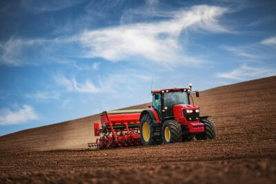 Fototapet Bonde med traktor sådd grödor vid fältet