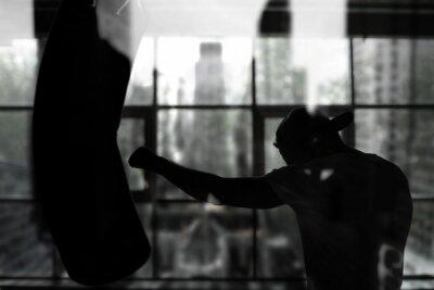 Fototapet Boxer träffar en boxningssäck mot fönstret, utbildning