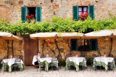 Fototapet Café bord och stolar utanför en stenbyggnad i Toscana