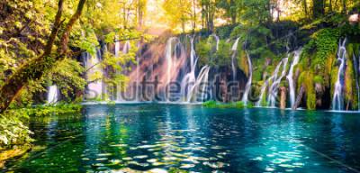Fototapet Det sista solstrålet lyser upp det rena vattenfallet på Plitvice National Park. Färgglada våren panorama av grön skog med blå sjö. Stor landsbygd utsikt över Kroatien, Europa.