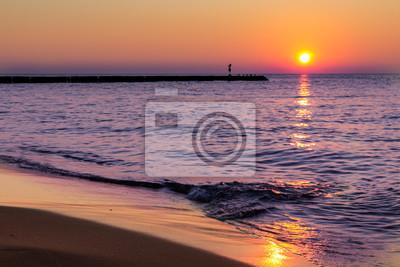 Fototapet En lugn, fridfull solnedgång vid havet och mjuka vågor stänk på stranden.